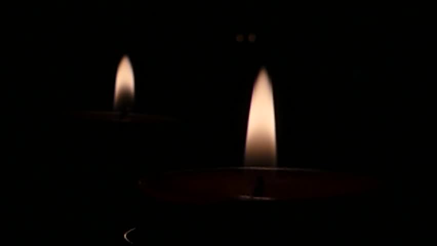 The fire from two candles in the dark. Windy in church. - HD stock footage clip