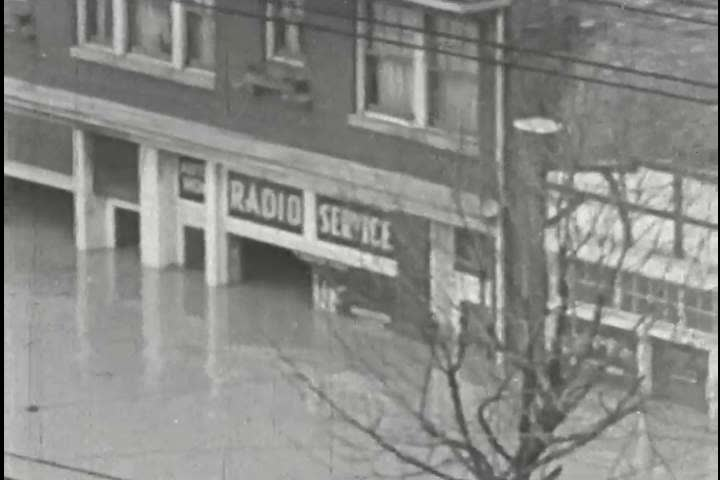 CIRCA 1930s - Men load goods onto row boats in flooded Louisville, Kentucky in the 1930s.