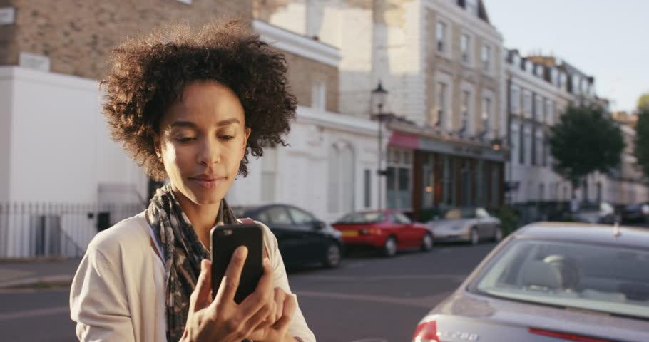 Beautiful Mixed race woman using smart phone technology app walking through city streets living urban happy lifestyle
