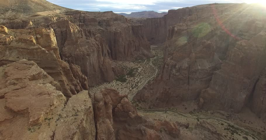 Aerial drone scene of big canyon in Patagonia, Argentina. Camera moves along the valley with high altutude. Evening time. Monumental natural landscape. #13910474