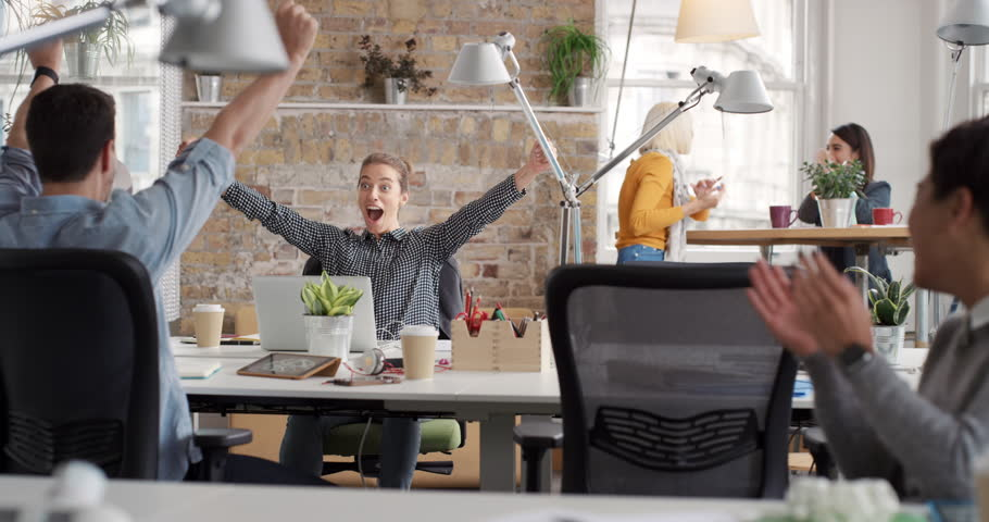 Business woman with arms raised celebrating success watching sport victory on laptop diverse people group clapping expressing excitement in office | Shutterstock HD Video #13947473