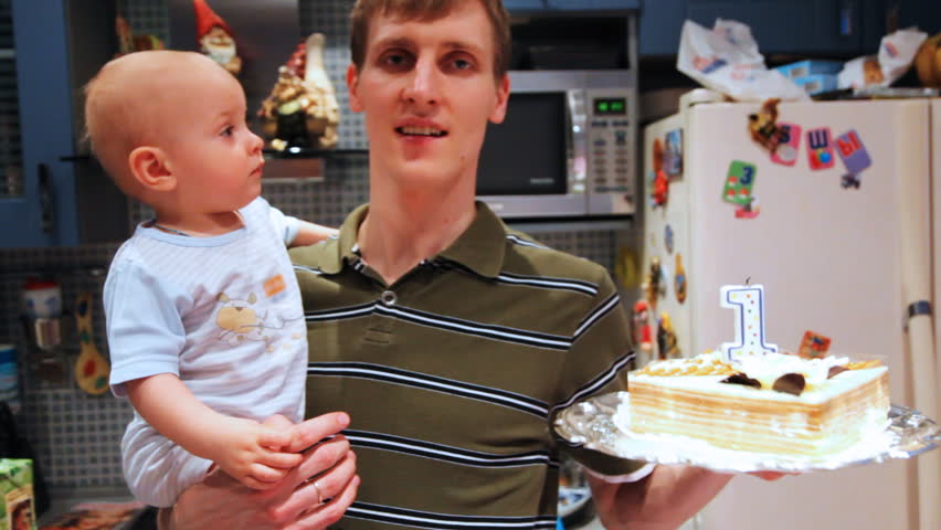 little baby in fathers hands try catch birthday cake on one year old - HD stock footage clip