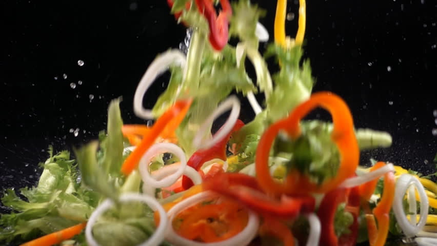 fresh vegetables falling with water on black background in slow motion