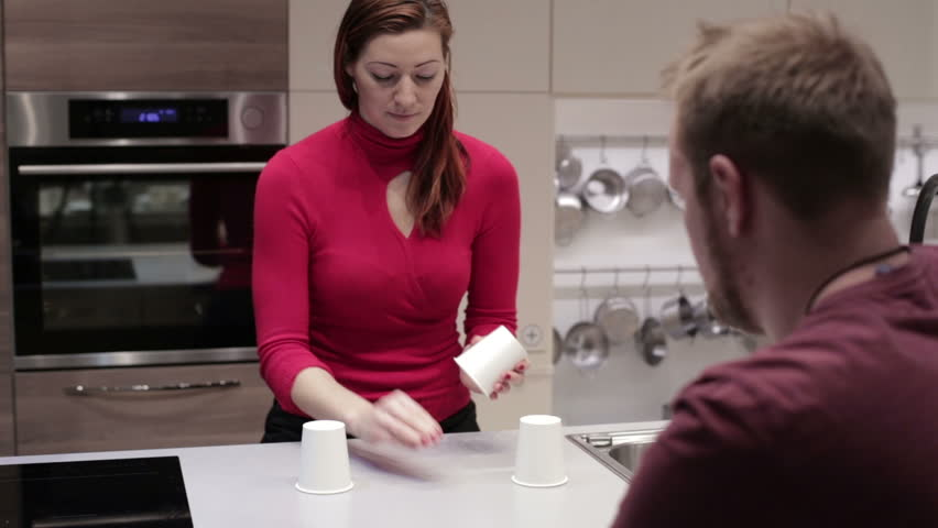 Couple playing a game with three glasses and ball - HD stock footage clip