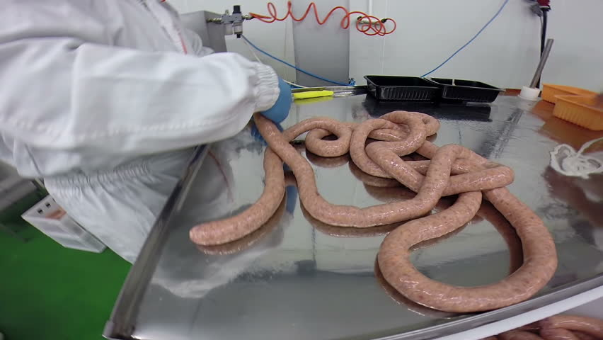 Butcher Making Fresh Sausages/Skilled butcher at work making sausages in meat industry.
