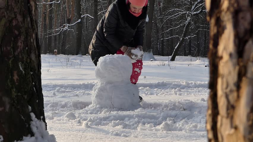 The girl makes snowman in winter in the woods.  Bark of pine on foreground.  - HD stock video clip