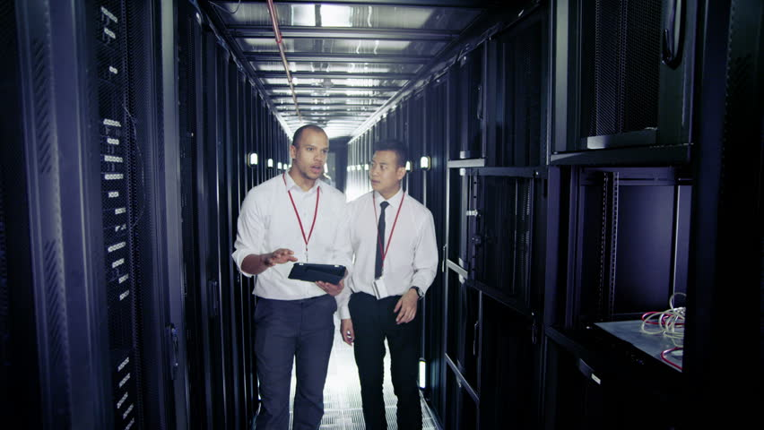 4k / Ultra HD version Team of people working in a data center with rows of server racks and super computers. They are looking into data cabinets and checking cables and other equipment. In slow motion