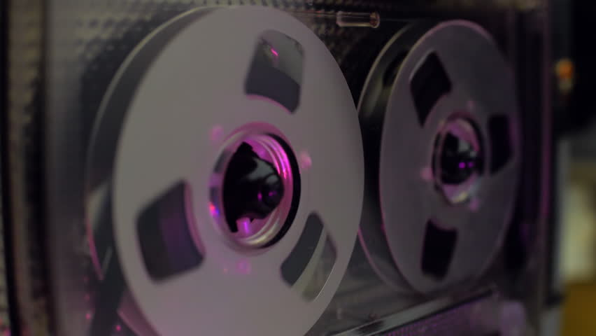 Rotation silver color reels of vintage audio cassette is glistens in the light. Closeup. Shallow depth of field