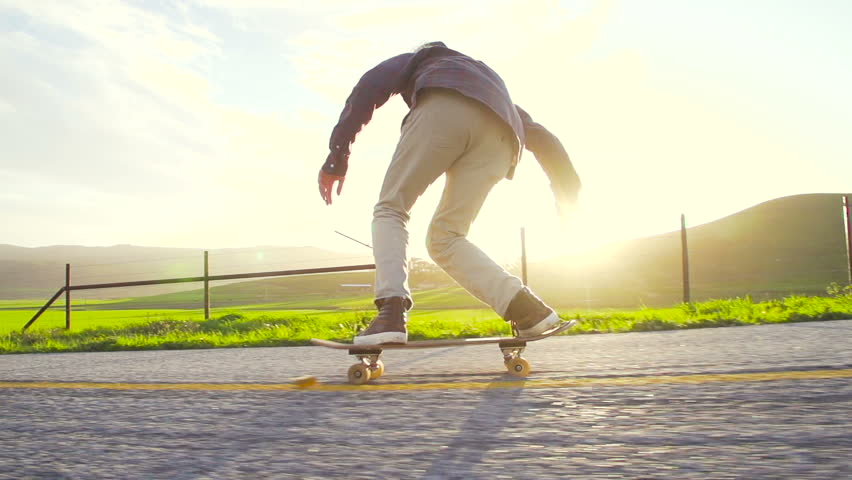 Slow Motion Skateboarder Riding Down Hill At Sunset