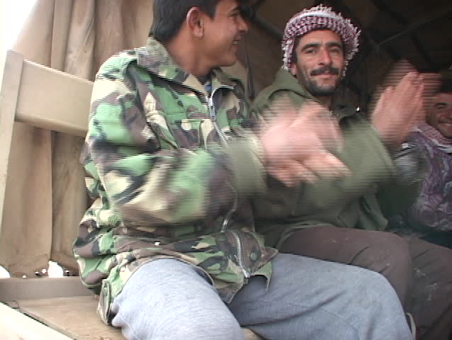 IRAQ - CIRCA 2003: Iraqi workers clap their hands and celebrate in the back of an Army Humvee circa 2003 in Iraq.
