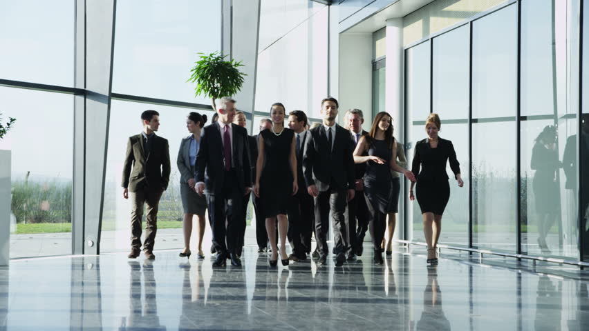 4k / Ultra HD version Portrait of an attractive multi-racial business team, as they walk through a light and modern glass fronted office building towards the camera. In slow motion. Shot on RED Epic - 4K stock video clip