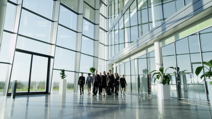 4k / Ultra HD version Portrait of an attractive multi-racial business team, as they walk through a light and modern glass fronted office building towards the camera. In slow motion. Shot on RED Epic - 4K stock footage clip