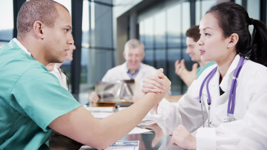 4k / Ultra HD version A team meet in a light, modern healthcare facility. One male nurse and one female doctor are bored and decide to arm wrestle each other. In slow motion.  | Shutterstock HD Video #14127419
