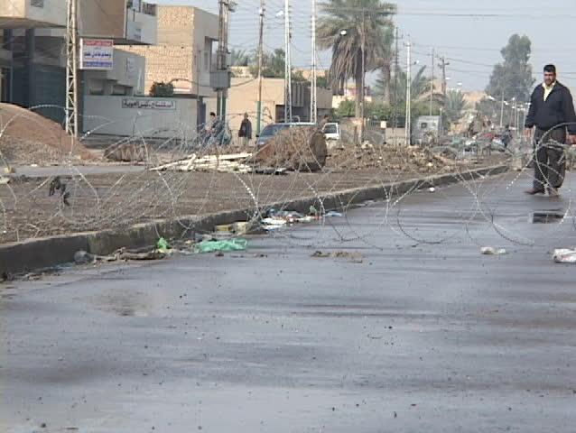An Iraqi man stands guard at a crude roadblock on a war-torn Baghdad street.
