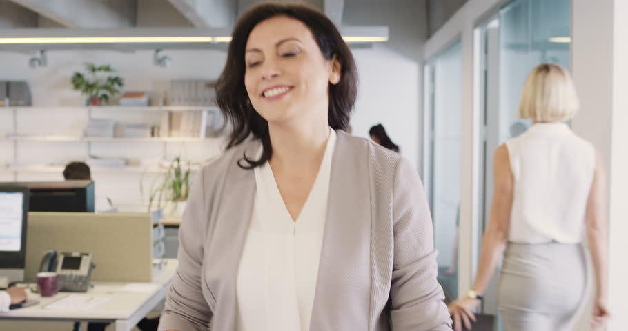 Beautiful businesswoman checking smart watch leaving busy office meeting achievement success smiling happiness