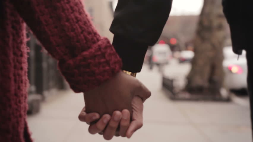 Girl and boy teenage young black couple walking together holding hands from a rear view perspective | Shutterstock HD Video #14150630
