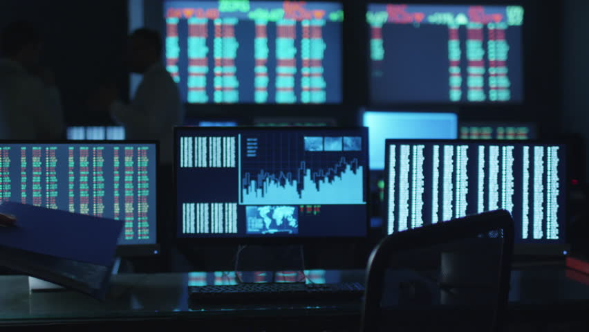 Stockbroker in white shirt is working in a dark monitoring room with display screens. Shot on RED Cinema Camera in 4K (UHD).