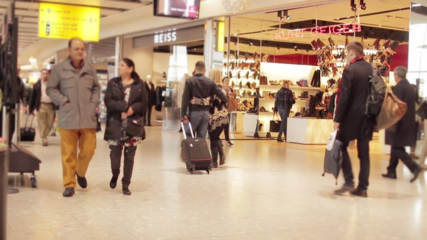LONDON, ENGLAND - 06 DECEMBER 2015: Travelers people crowd airport stores - Crowd walking at the Heathrow airport, England - 1080p