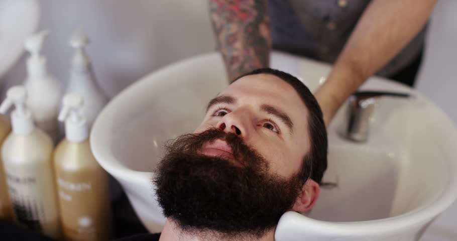 Young hipster man having his hair washed at a hair salon.  | Shutterstock HD Video #14220929