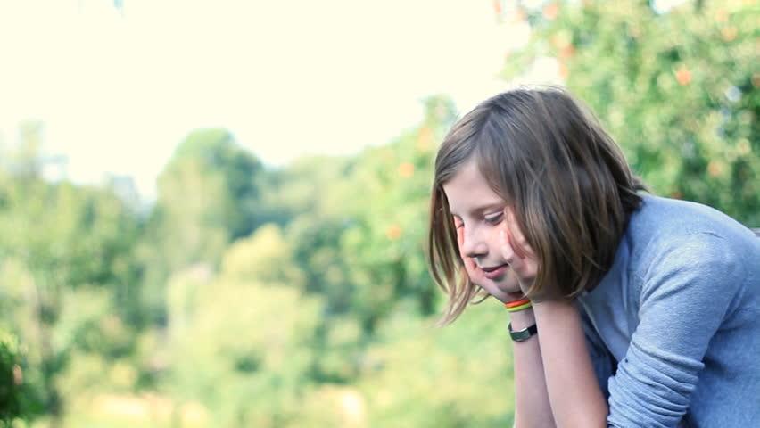 Sad Teenage Girl Sitting On Bench Outdoors, Dolly Shot ...