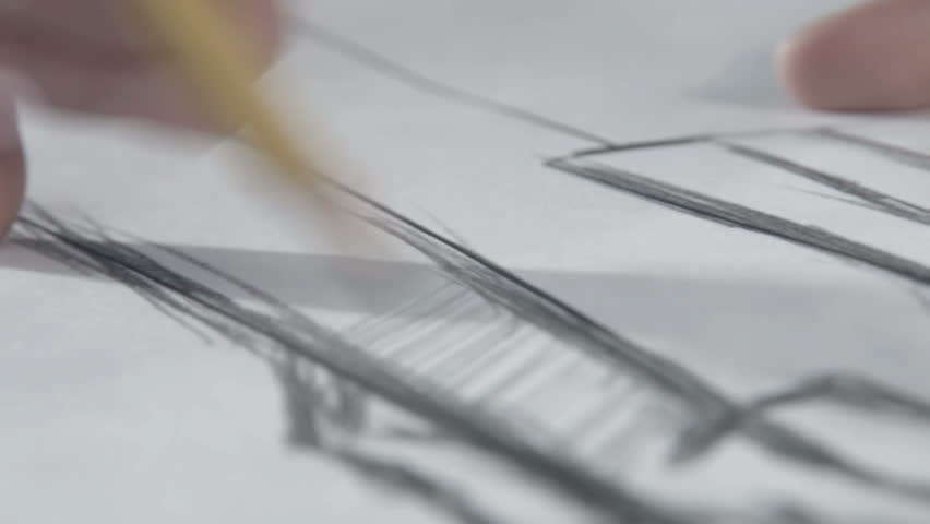 Hand of female tailor drawing pattern at paper in her studio. woman's hand draws a pencil. Designer clothes or tailor, animator, artist or illustrator. It looks like a geometry or drawing