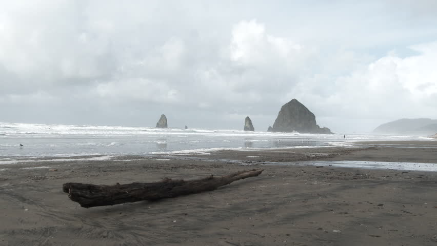 Rain clouds and high winds keep people indoors at the Oregon Coast by Haystack Rock in Cannon Beach, Oregon.