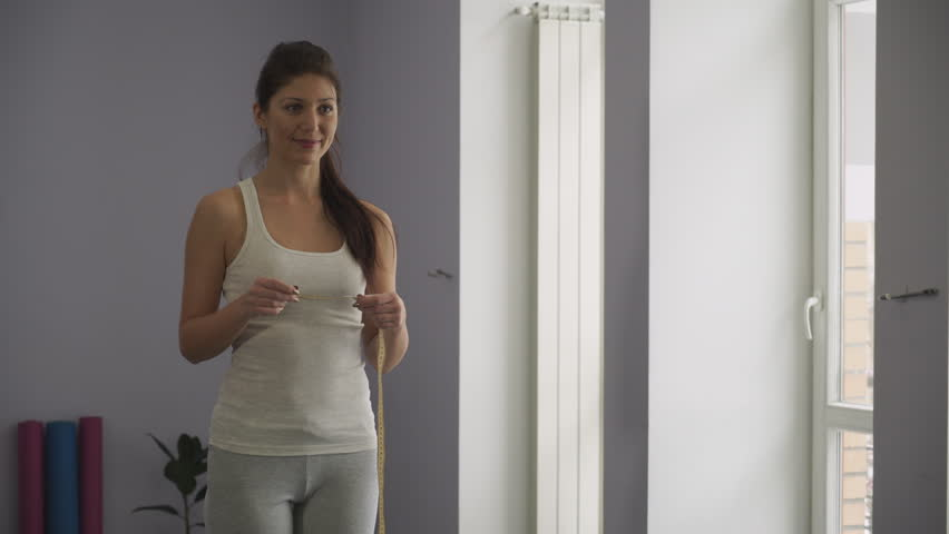 The girl measures the waist in the gym. Soft panorama | Shutterstock HD Video #14258369