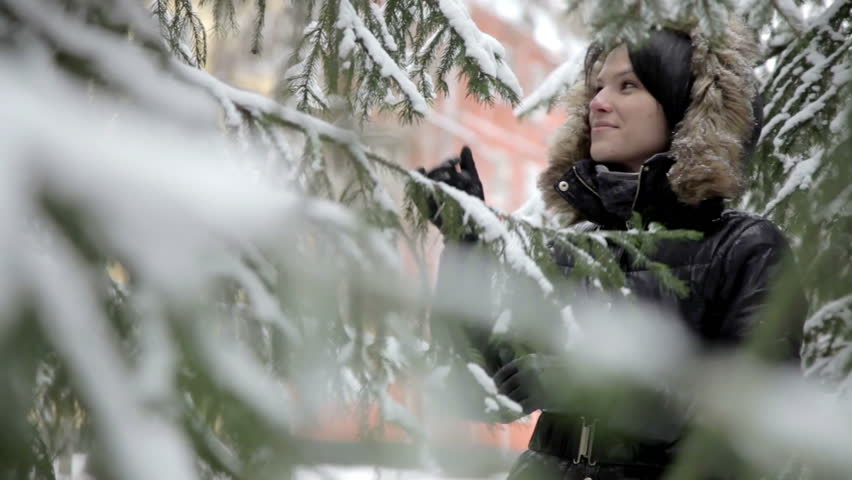 Portrait of a cute brunette girl with black hat smiling behind pine branches on mountain under snow on a sunny winter day. - HD stock video clip