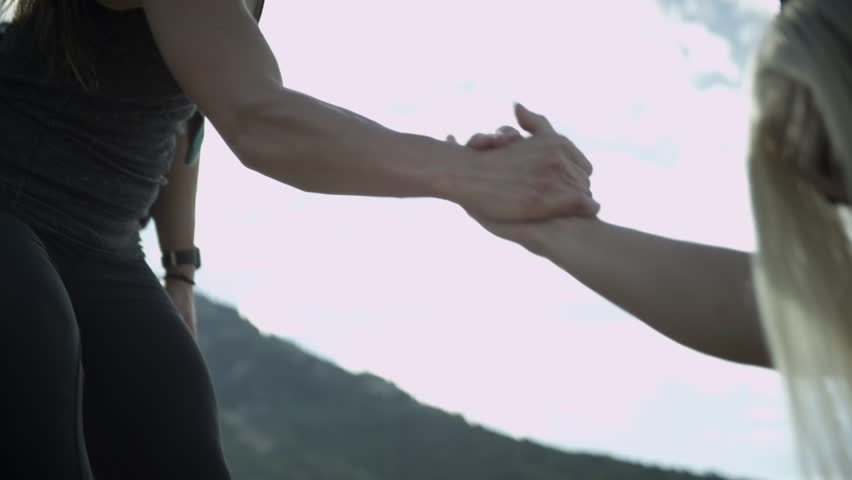 Woman helping another woman up the path. | Shutterstock HD Video #14275307