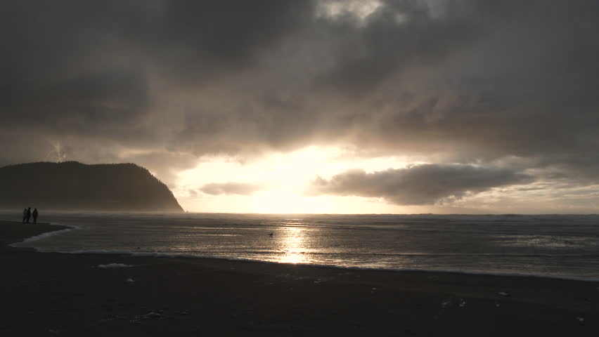 A break in the clouds brings sunshine to the horizon at the Oregon Coast in Seaside.