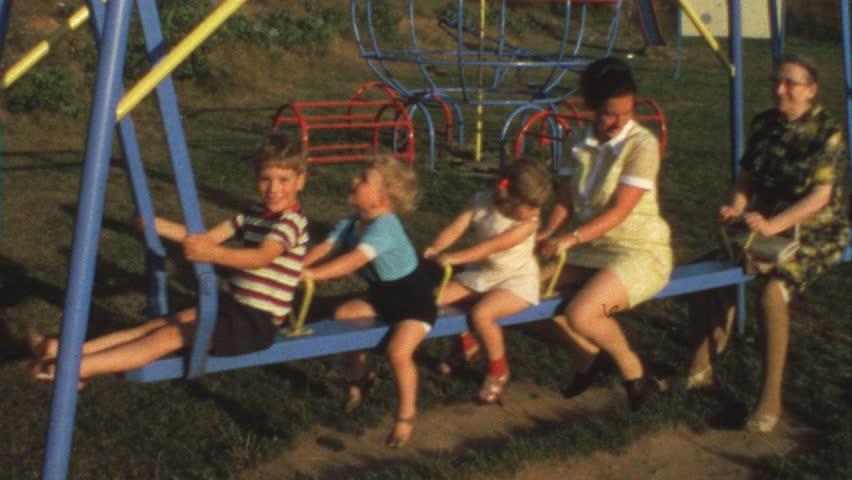 Mother, grandma and children on swing (vintage 8 mm film)