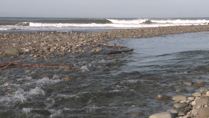 Water flowing out of the Ventura River estuary into the Pacific Ocean in Ventura, California. - HD stock video clip