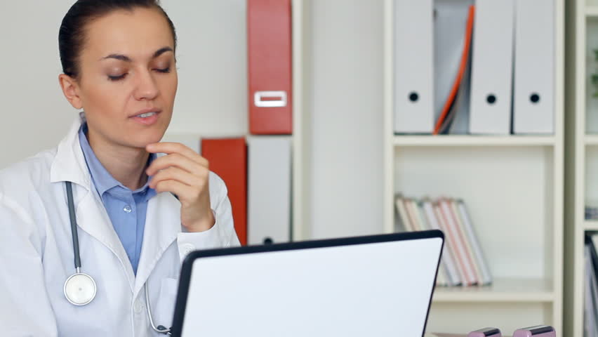 Overworked female doctor sitting at the desk and yawn - HD stock video clip