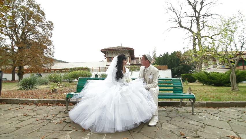 Crimean Tatar newlyweds sitting in the park Bakhchisaray Palace (Hansaray, Khan's Palace) Bakhchisaray, Crimea, Ukraine. lockdown - HD stock footage clip