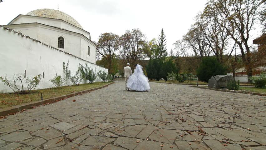 Crimean Tatar newlyweds walking through the park Bakhchisarai Palace (Hansaray, Khan's Palace) Bakhchisaray, Crimea, Ukraine.  - HD stock footage clip