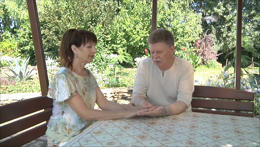 Happy elderly man and woman sit in the gazebo - HD stock footage clip