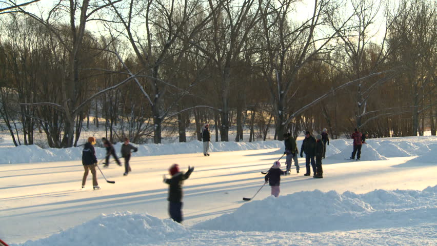 family ice skating on outdoor rink,