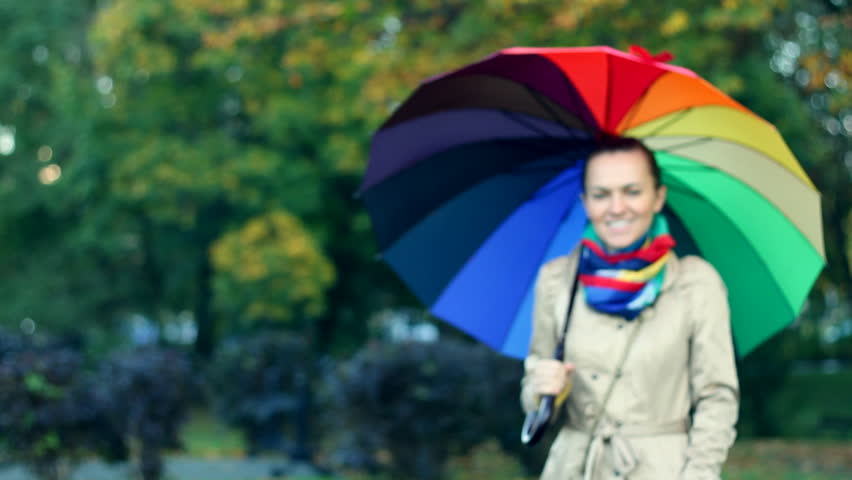 Woman walking with colorful umbrella - HD stock video clip