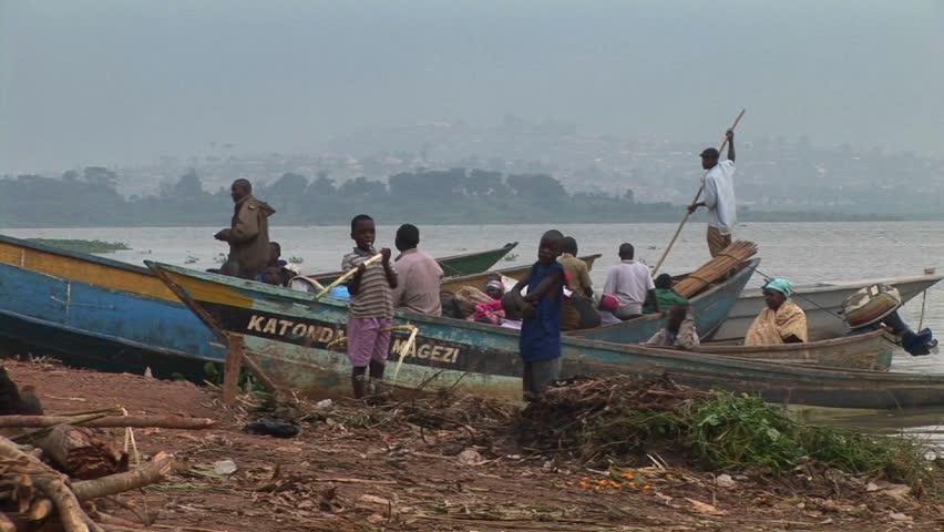 LAKE VICTORIA, UGANDA - CIRCA 2009: Boys stand before fishing boats at Gaba village, along the shores circa 2009 iat Lake Victoria. - HD stock video clip
