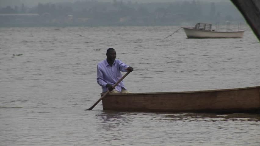 LAKE VICTORIA, UGANDA - CIRCA 2009: A man rows a fishing boat circa 2009 in Lake Victoria. - HD stock footage clip