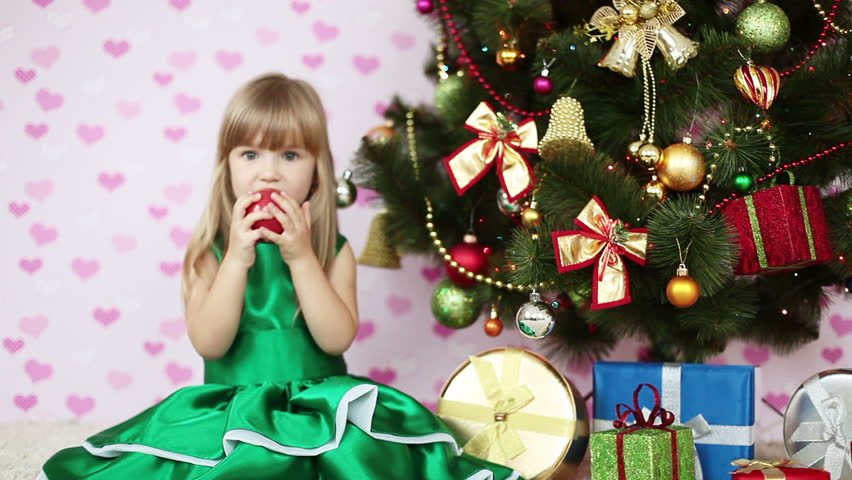 Girl eating an apple near a Christmas tree. She sits on the floor - HD stock footage clip