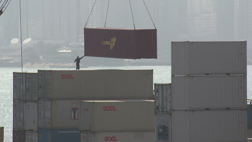 HONG KONG - CIRCA JUNE 2010: Dock worker guides shipping containers into place in port in Hong Kong circa June 2010. - HD stock video clip