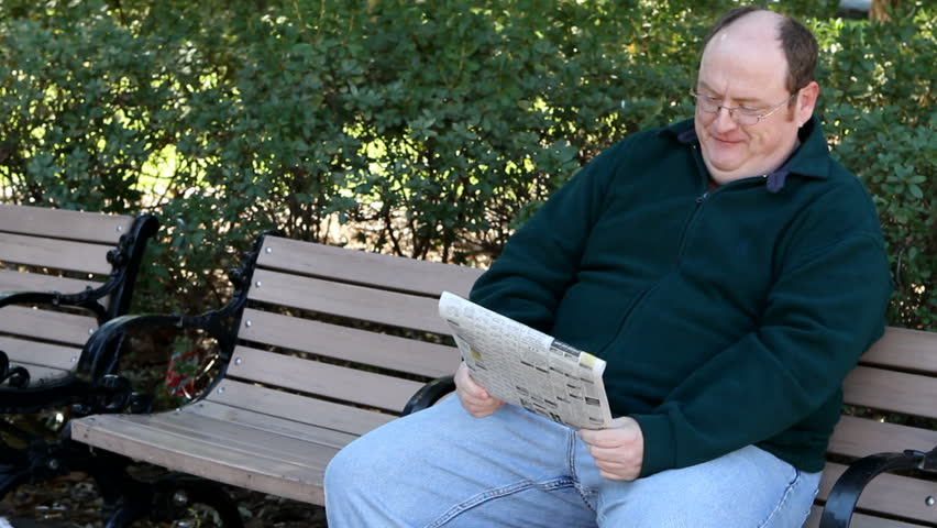 Overweight man sits on a park bench reading the newspaper. - HD stock video clip