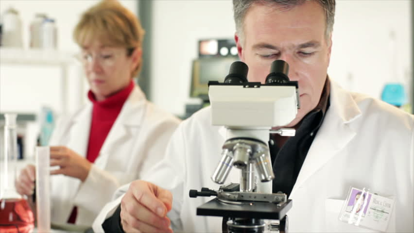A woman and man who appear to be scientists or chemists working in a laboratory using microscopes and other technologies. - HD stock footage clip
