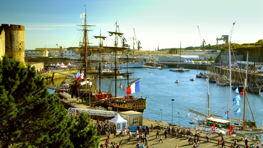 Brest, France - July 14, 2016: Old ships in timelapse: Etoile du Roy, Hermione, Cuauhtemoc in the harbor of Brest. Crowd, french flags and small boats moving fast. Colorful scenery at Golden hour.