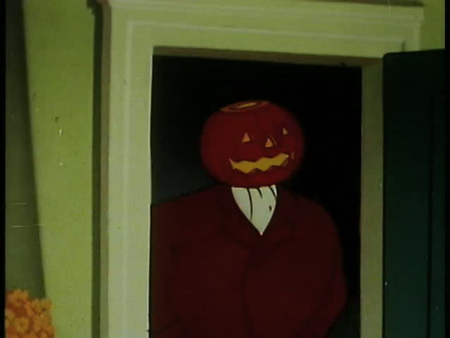 Man with pumpkin head standing in doorway