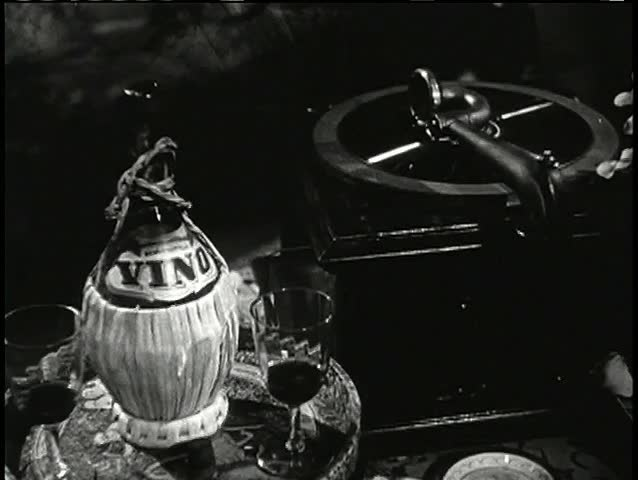 Gramophone next to tray with wine bottle and glasses