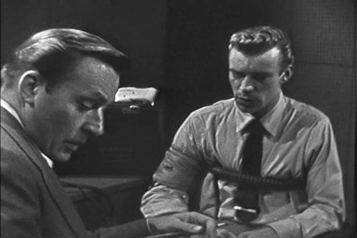 A polygraph technician explains the interrogation process to a jewelry store employee accused of theft in the 1950s. (1950s)