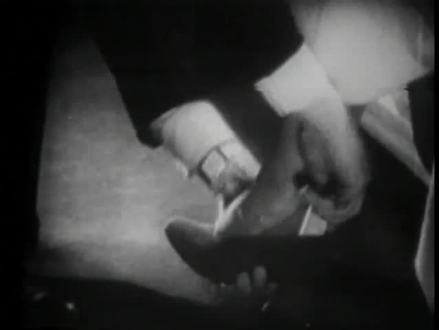 Salesman helping woman try on shoes