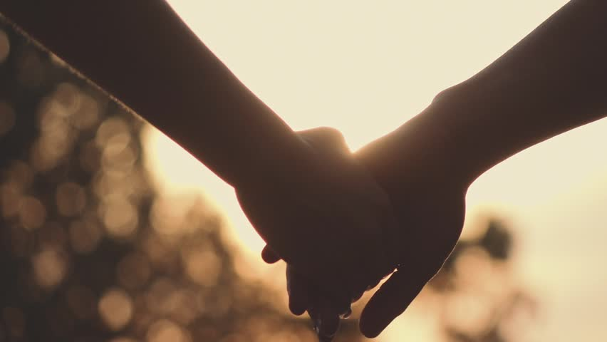 Close up of two Lovers Joining Hands. SLOW MOTION 240 fps. Detail Silhouette of Man and Woman holding hands over the Sunset Lake Background. Couple Trust, Love and Happiness concept. | Shutterstock HD Video #18598151